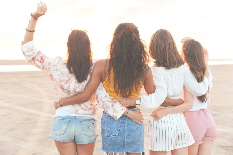 Four girls looking at the sunset together on the beach.
