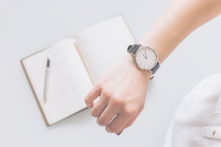A person looking at their watch with a notebook on a table.