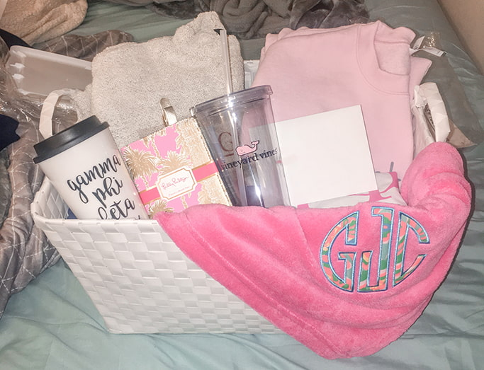 The Initiation gift basket I gave my first sorority little. It has a lot of Gamma Phi Beta items in it, like a blanket, to-go coffee cup, two sweaters, a Vineyard Vines cup, and a Lilly Pulitzer passport holder.