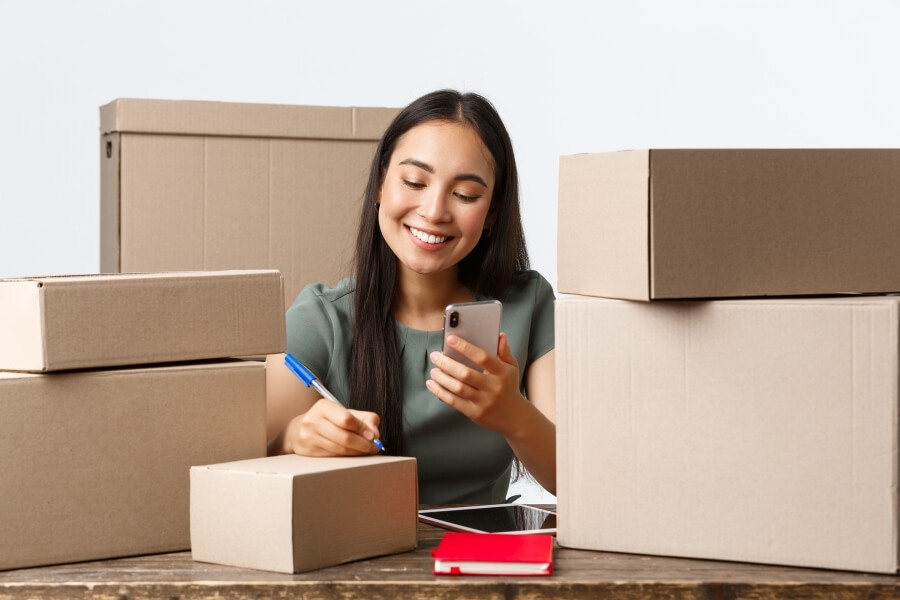 A young woman surrounded by moving boxes on her phone.