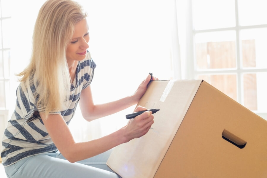 A young woman writing a label on her moving box. She is moving out of her parent's home.