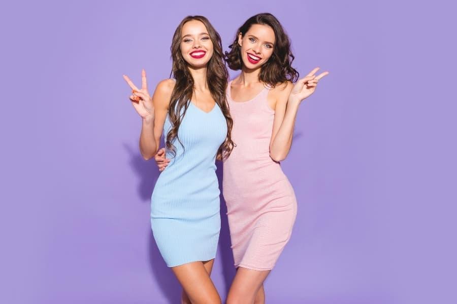 Two upperclassmen posing against a purple backdrop before going through sorority recruitment.