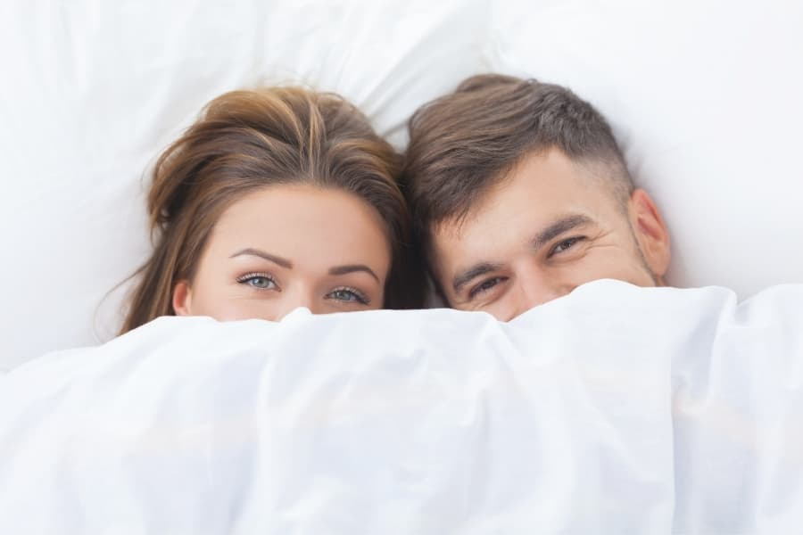 A guy and a girl in bed after being intimate, which is an topic you should avoid during sorority rush.