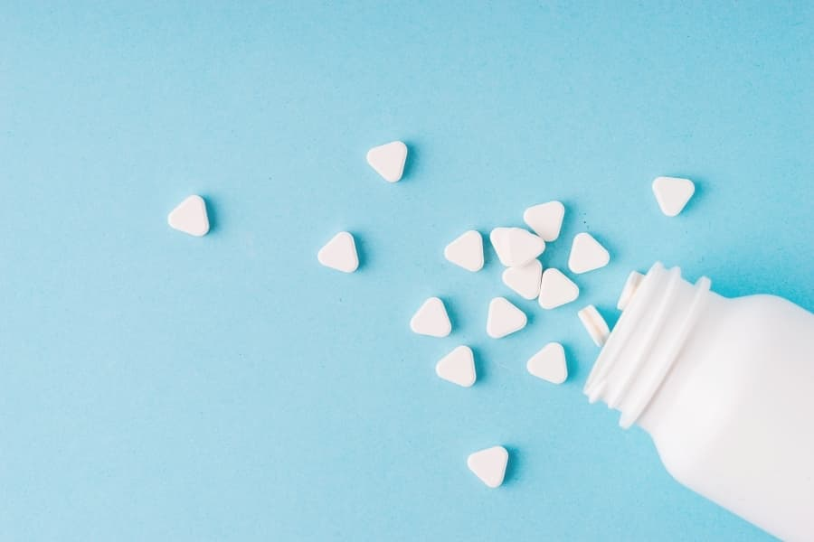 A bottle of pills in the shape of hearts on a blue backdrop. And drugs is another topic you should not talk about during sorority rush.