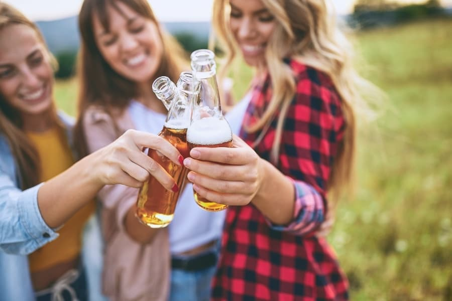 A group of young women outside enjoying beers, which is a topic you should not discuss during sorority recruitment with potential new members or sorority sisters.