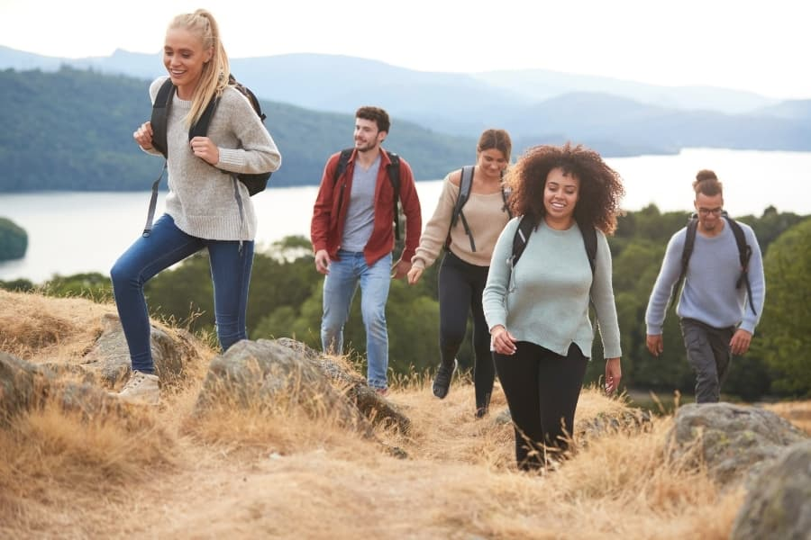 Five college graduates hiking up a mountain together as a way to make friends after college.