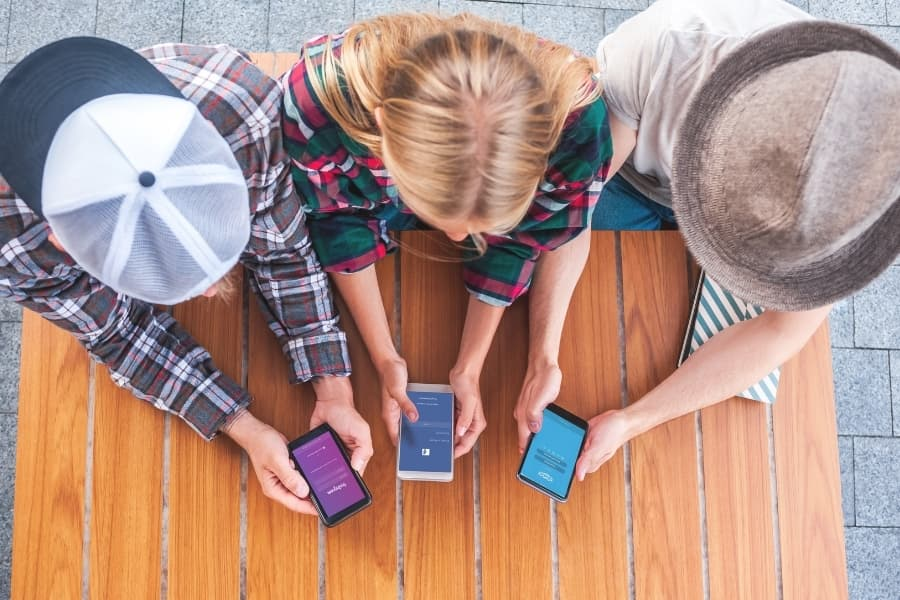 Three friends using social media apps to make friends after college.