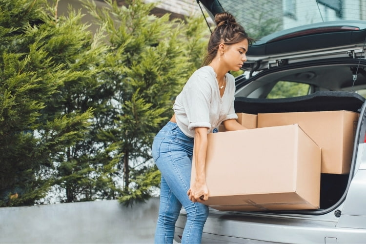 A girl wearing comfy clothes on college move-in day and is packing her car.