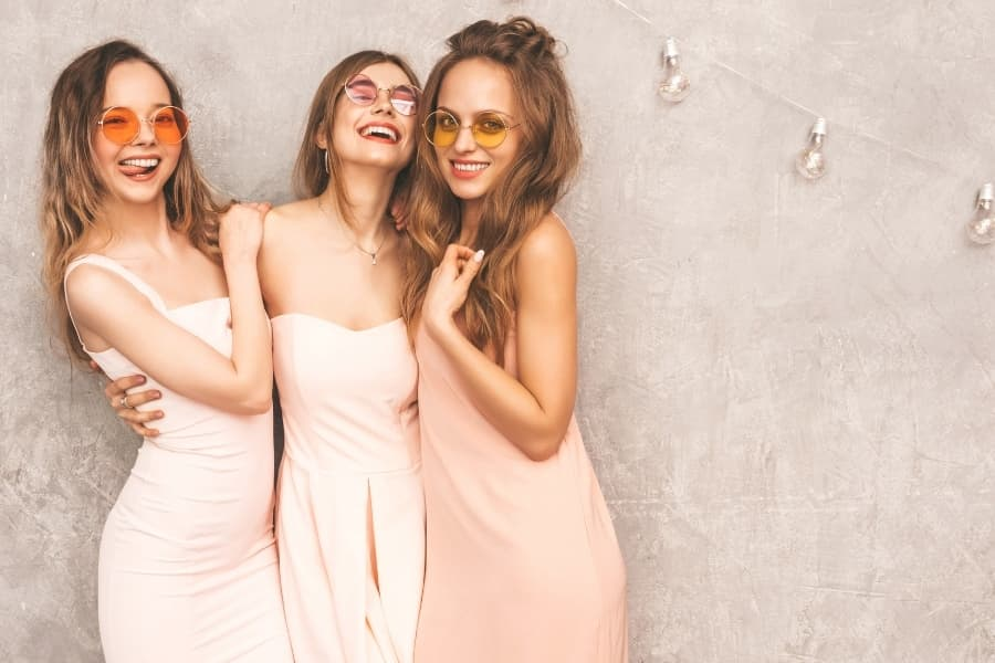 Three sorority women in dressing posing for a picture.