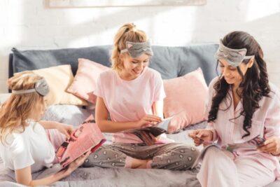 Three sorority women reading magazines in their PJs in their Sorority House